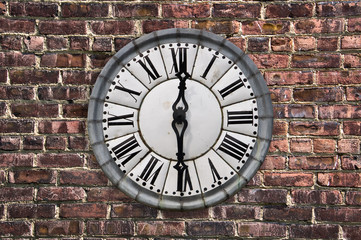 Vintage retro style clock on a red brick wall
