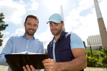 Electrician and engineer checking calendar at the electric stati