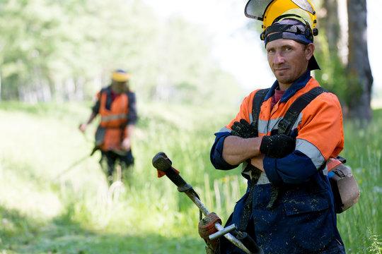 Portrait positive landscaper during grass cutting team works