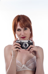 Portrait of young woman taking a photo using an old camera
