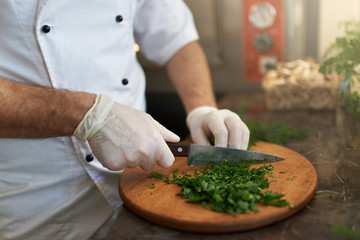 Cook chops fresh herbs on  wooden board