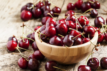 Fresh cherries in a wooden bowl, selective focus