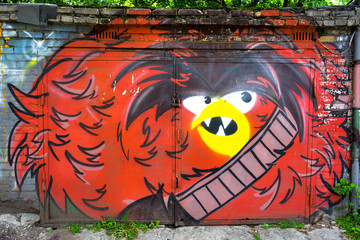 Street art or angry red bird graffiti by unidentified artist in the garage doors