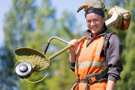 Portrait happy gardener man worker with gas grass trimmer equipment