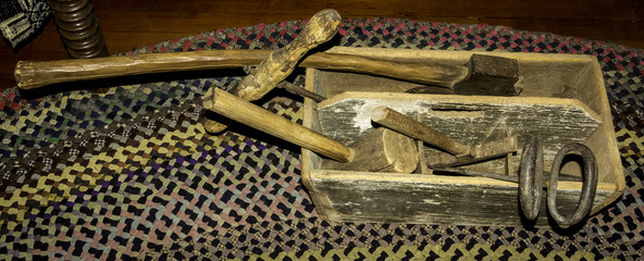 Antique tools in a wood tool box on the floor