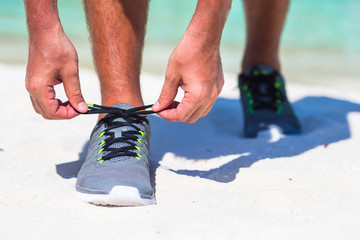 Running man tying running shoe laces on white beach