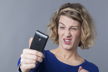 20s blonde girl disappointed about her image on smartphone