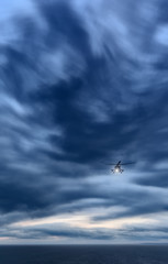 Storm at sea, Mi-8 helicopter from below in front dramatic sky,