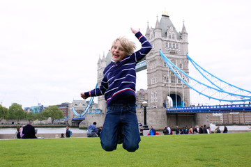 School boy jumping on the lawn in front of beautiful Tower Bridge and River Thames on a sunny summer day, London, UK. Happy caucasian tourist kind enjoying view during family trip to England.