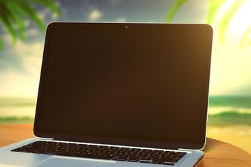 Blank laptop on the beach in summer