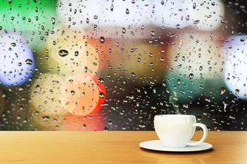 coffee cup on the background of the window with raindrops