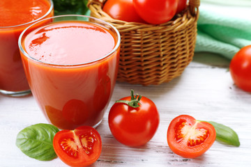 Glasses of fresh tomato juice on wooden table, closeup