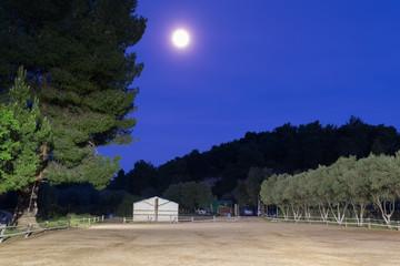 Horse arena against full moon.