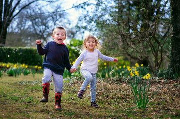 Two happy little friends kids boy and girl playing in blossoming