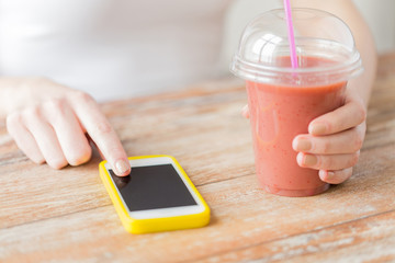 close up of woman with smartphone and smoothie