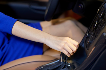 close up of woman shifting gears on gearbox in car