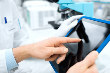 close up of scientists hands with tablet pc in lab