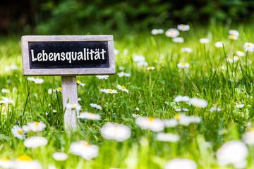 Schild in der Wiese mit Aufschrift Lebensqualität