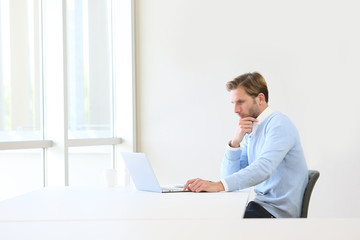 Thoughtful businessman working on laptop in business room