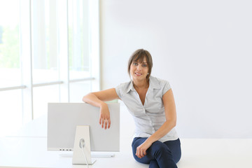 Smiling young woman sitting on table by computer
