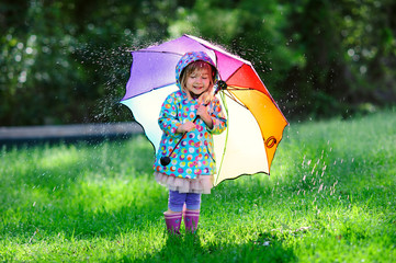 cute toddler girl wearing waterproof coat with colorful umbrella