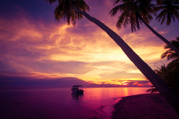 Tropical island in the sunset with a boat