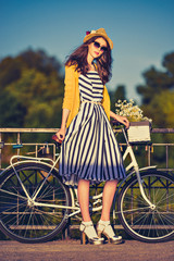 Young beautiful, elegantly dressed woman with bicycle. Beauty