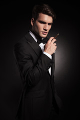 Young elegant man holding a cigarette in his hand.