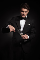 Young elegant man pouring wine in a glass
