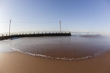 Beach landscape ocean wave water across sand around tidal pool