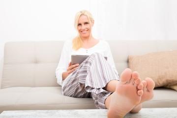 Reife Frau mit Tablett pc auf dem Sofa