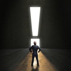 Geschäftsmann steht vor einem leuchtenden Ausrufezeichen-Durchgang