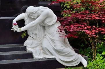 Frauenfigur aus weißem Marmor vor Grabmal