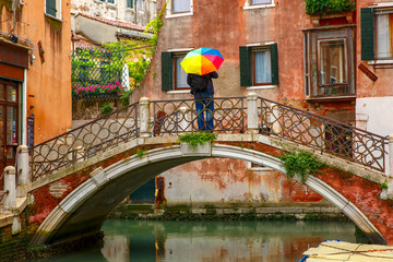 Poster Channel Man with umbrella on bridge over Venetian canal