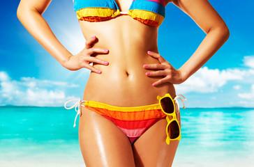 Beautiful woman body with colorful bikini on the beach.