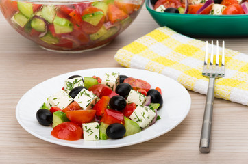 Transparent glass bowl and plate with Greek salad, fork