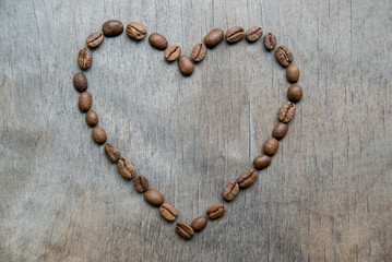 Heart of coffee beans on wooden background
