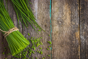 Fototapeta bunch of  chives on a wooden cutting board obraz