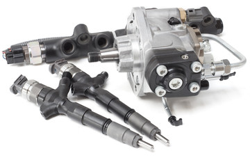 Two new solenoid injectors for diesel fuel lying on a white background with a rod and a fuel injection pump