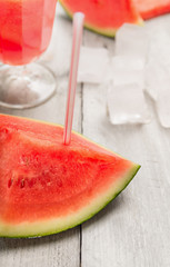 slice of watermelon with drink straw on drinks and ice background, close up