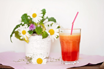Strawberry, orange and apple fresh in a glass with a lined straw
