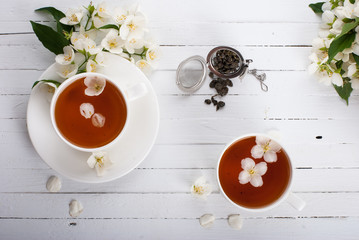 A cup of green tea with jasmine on a white surface