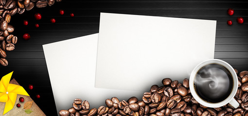 Coffee cup and coffee beans on a black wooden table. Dark background