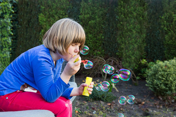 Young dutch girl blowing bubbles from soapy water