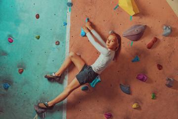 Sporty little girl climbing indoor