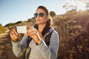 Hiker woman taking photographs with her smartphone