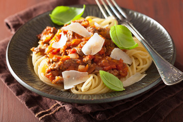 italian pasta spaghetti bolognese with basil on rustic table