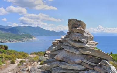 tas de pierre sur sentier en bord de mer - Cap Corse