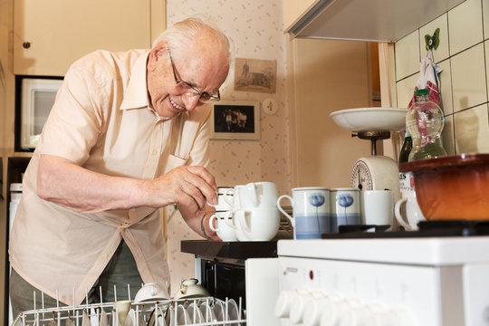 Elderly man unloading the dishwasher
