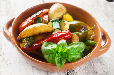 Delicious baked vegetables on a wooden background